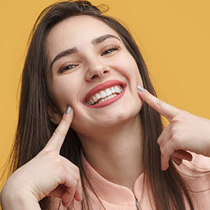 A woman points to her smile after getting cosmetic dentistry in Webster, TX