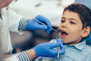 A boy sits in a dentist's office as he receives pediatric dentistry in Webster, TX