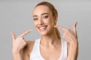 happy woman pointing to her conventional dentures