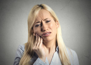 woman struggles with the the pain caused by impacted teeth